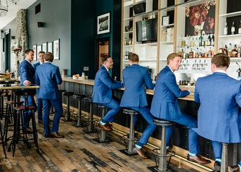 7 guys in matching blue suits drink cocktails and chat at a modern bar