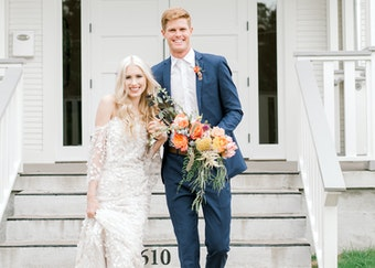 groom in a blue suit walking with bride in a white wedding dress holding flowers