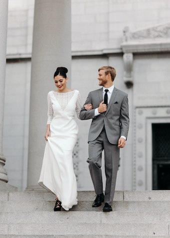 groom in a grey Menguin suit and black tie walks down steps with bride