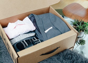 grey Menguin suit with a white pocket square folded nicely in its box