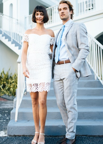 groom wearing a Menguin plaid suit with blue accessories and brown shoes standing next to bride in a simple bridal dress