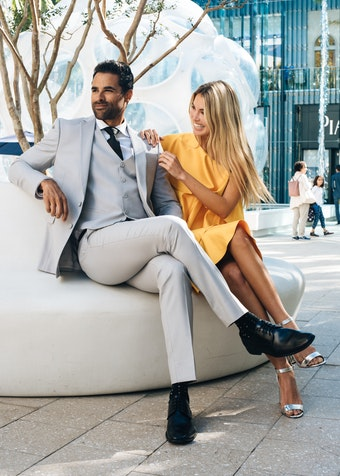 gentleman in a grey Menguin 3-piece suit with black shoes and tie sits outdoors next to a woman in a dress