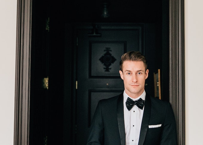 guy in a generation tux black shawl lapel tuxedo stands in an entryway