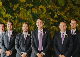 groom in his generation tux suit with a purple tie stands with his groomsmen