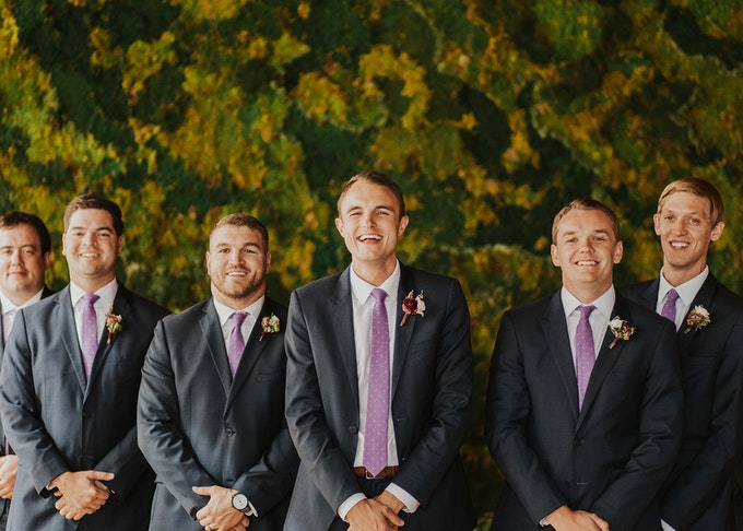 groom in his generation tux suit with a notch lapel and purple tie stands with his groomsmen