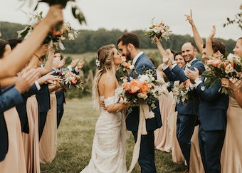 bride and groom in a generation tux blue suit kiss outside with bridal party