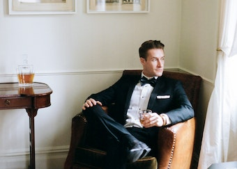 man in black generation tux outfit waiting for formal date