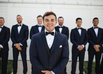 Groom in generation tux navy tuxedo with black lapel stands smiling in front of his groomsmen