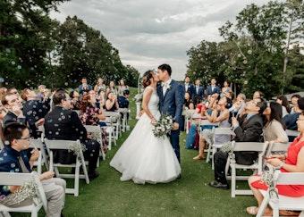 Groom in Mystic Blue Tuxedo Kissing Bride