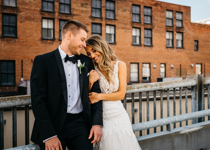 groom in tuxedo and bride embracing in front of brick building