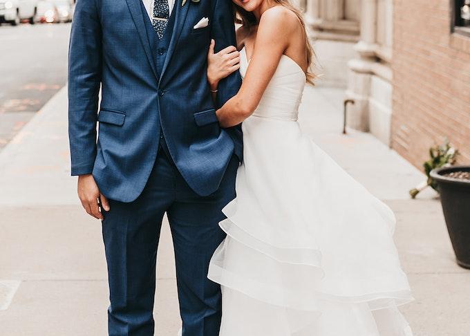 groom in blue suit and bride embracing on sidewalk