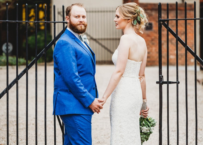 groom in blue suit and bride holding hands in front of wrought iron gate