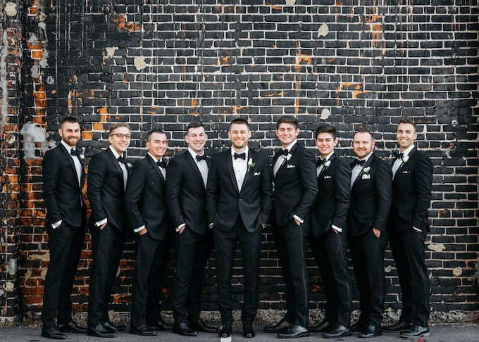 group of groomsmen in black tuxedos and black bow-ties
