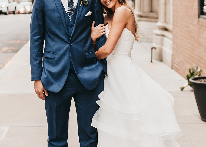 groom in blue suit with bride on sidewalk with Texas flag in background
