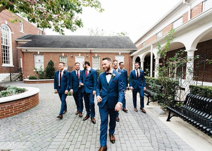 group of groomsmen wearing blue suits walking through courtyard