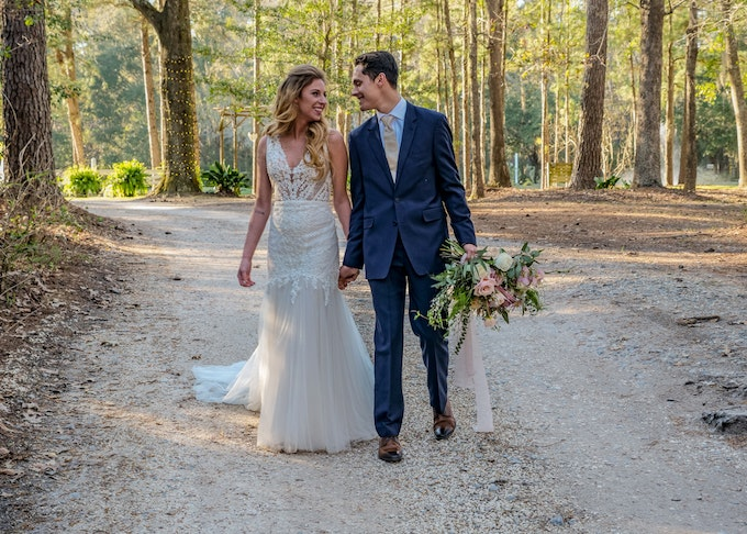 bride and groom in blue suit on dirt road in the woods