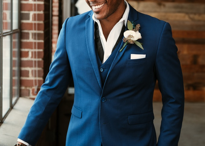 smiling groom in a blue suit