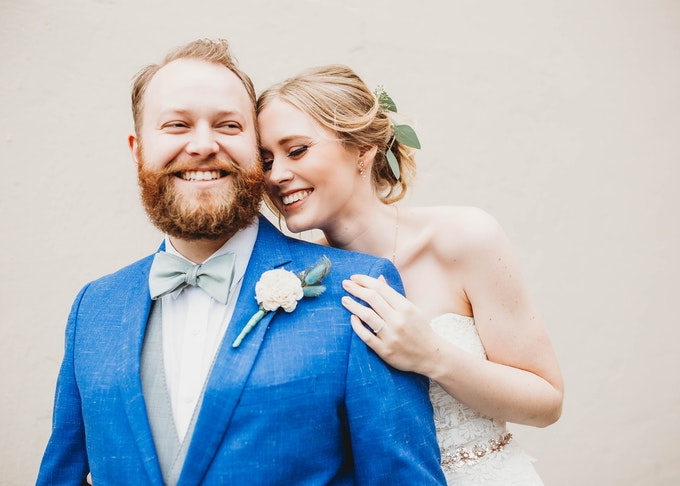 Smiling bride and groom wearing blue suit.