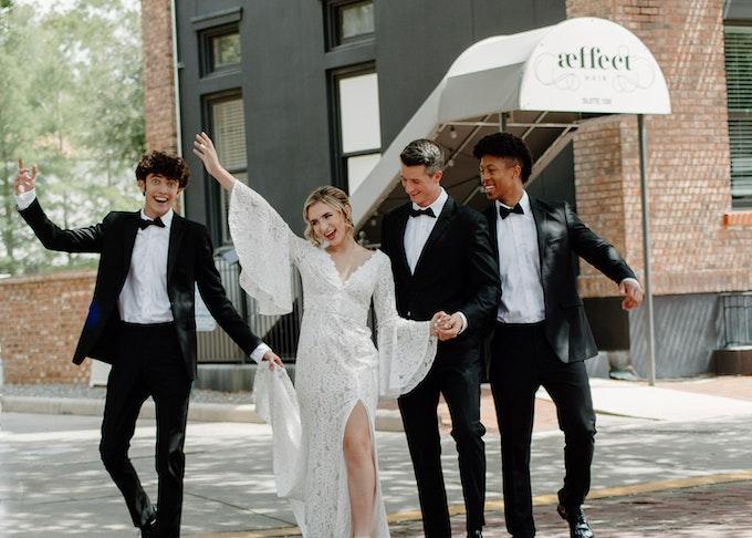 Bride and groomsmen in black tuxedos celebrate