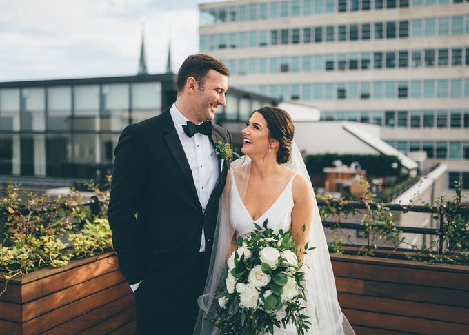 Smiling bride and groom in black tuxedo on a balcony