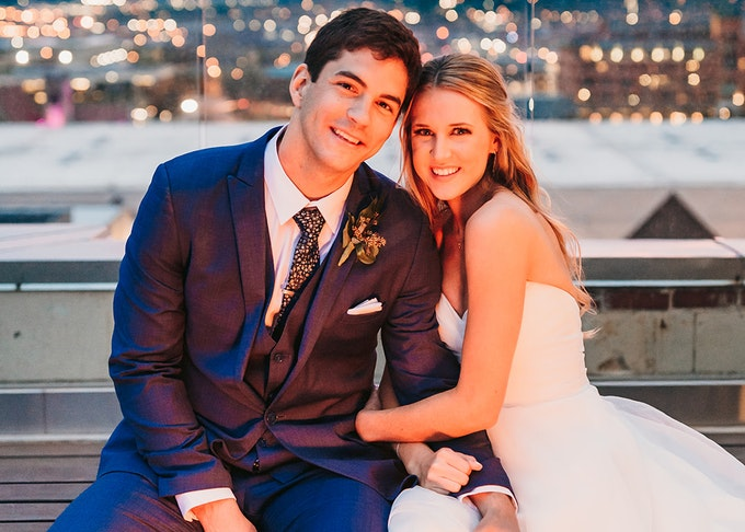 Bride and groom in blue suit on a balcony at dusk