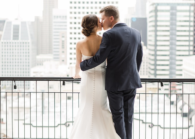 Bride and groom in blue suit kiss on a balcony overlooking the cityscape