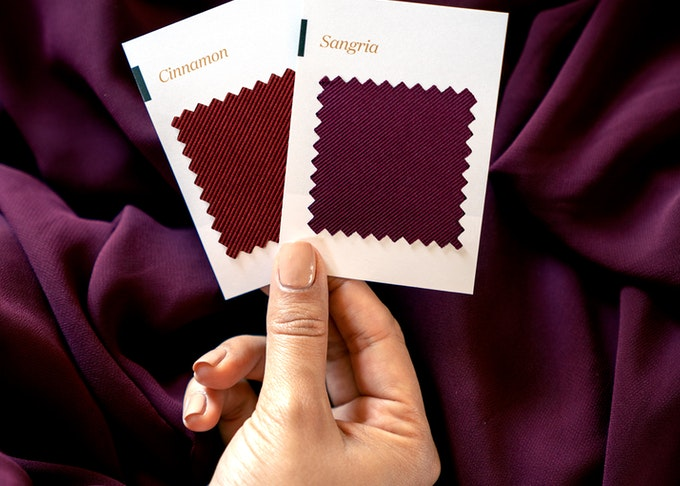 Hand holding Sangria and Cinnamon swatches