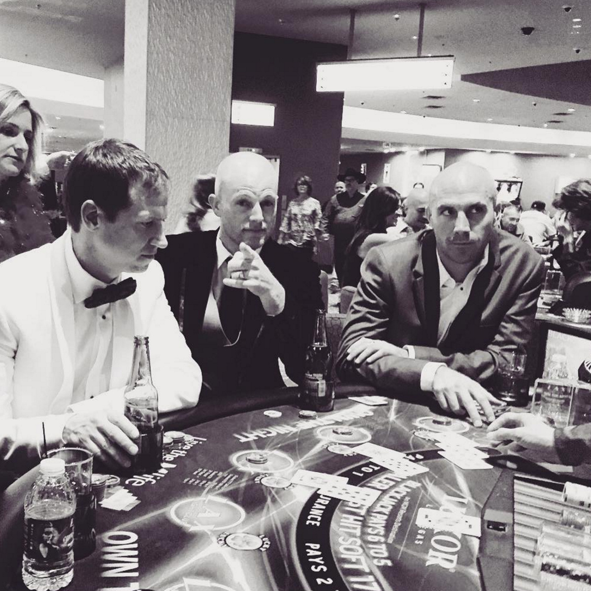 Black and white photo of 3 guys in suits sitting at a poker table.