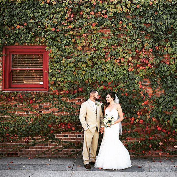 Bride and groom in front of a vide covered brick wall outside.