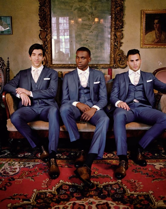Three guys wearing suits sitting on a bench in front of a vintage mirror and wall.