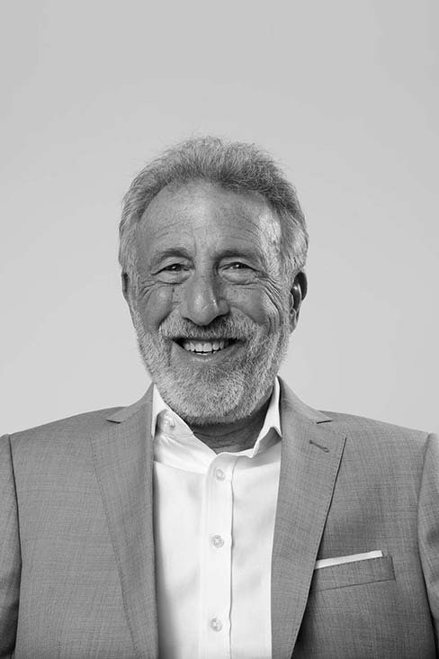 George Zimmer happily wearing a suite in a black and white photo.