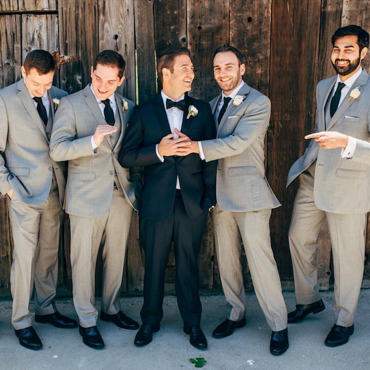 Groom and groomsmen in front of a wooden backdroom.
