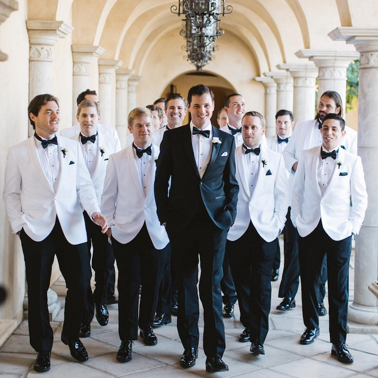 Grooms and groomsment in an outdoor hallway.