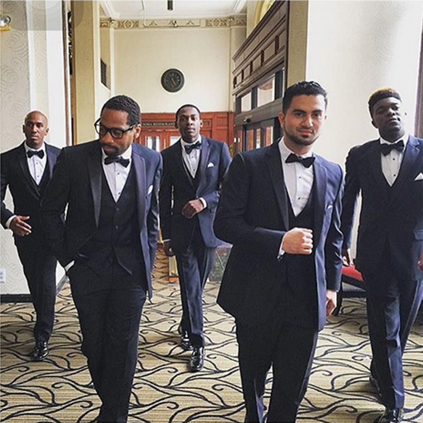 Groomsmen walking cool down a hallway in black suits.