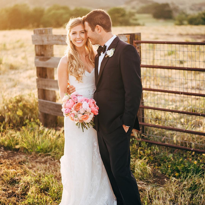Happy bride and groom in the field of a farm.