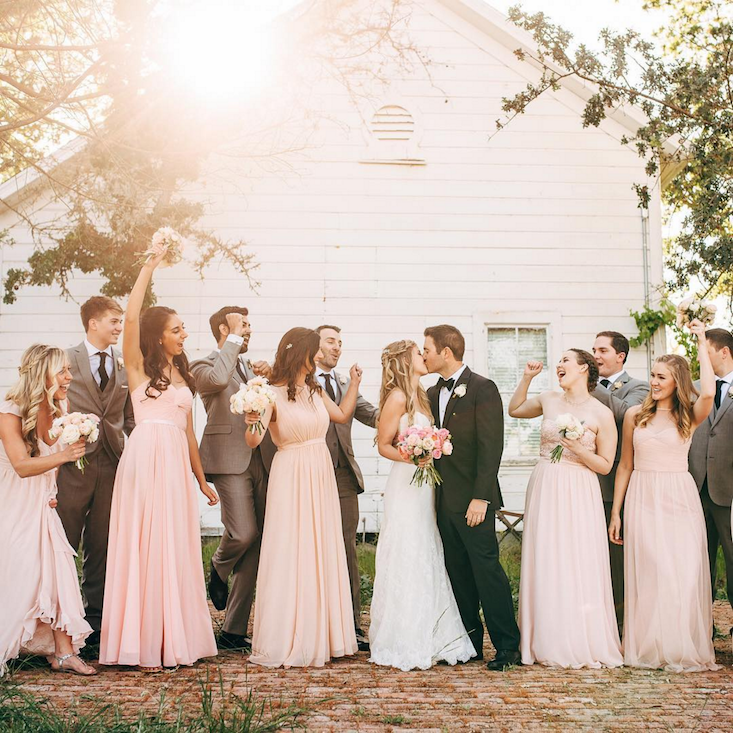 Happy wedding party celebrating outside.