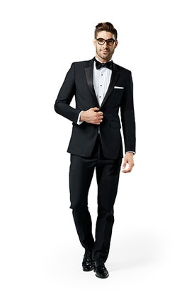 Black notch lapel suit worn in front of a white background.