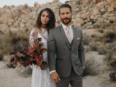 Wedding photo taken of the bride and groom smiling outside in the bright desert mountains.