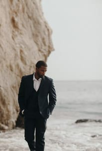 Photo of a lone groomsmen taking a walk on the beach with the rough waves in the background.