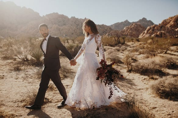 Couple getting married in Menguin Tux outside in the bright desert mountains.