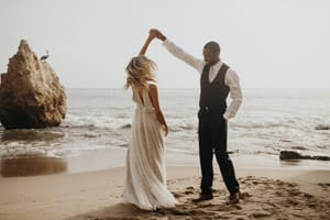 Wedding photo taken of the Bride and Groom dancing outside on the beach. The photo has a vintage feel too it.