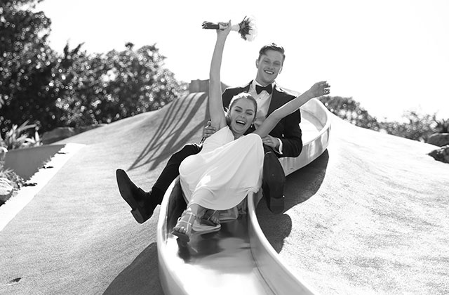 bride and groom riding a slide