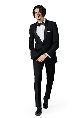 Black Shawl Lapel suit worn in front of a gray background.