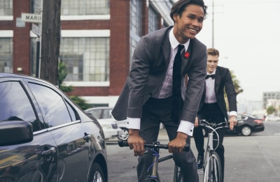 Guy on a bike outside in an urban setting wearing a grey suit.
